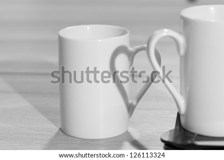 White cups on table with heart shadow - stock photo