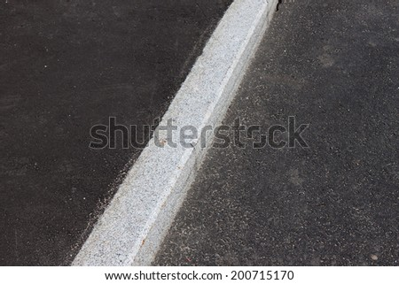 white curb stone border and asphalt road - stock photo