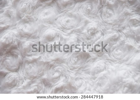 White curly faux fur texture background fragment, is generated from a material of clothes. Textured fabric background - stock photo