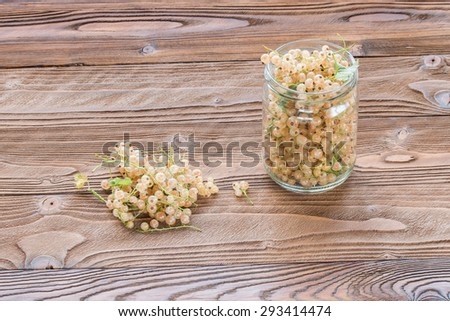 white currant in glass jar on wooden table at rustic style