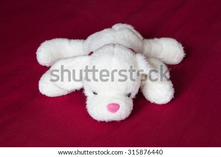 White cute dog doll on red fabric background