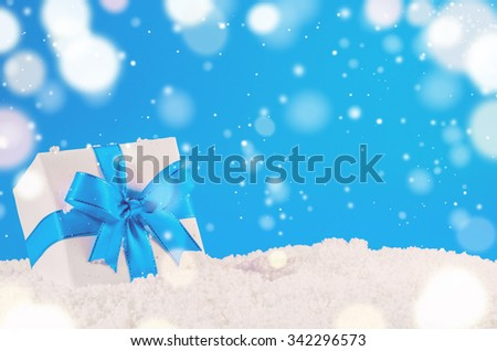 white decorative christmas gift box with ribbon on snow against blue festive background