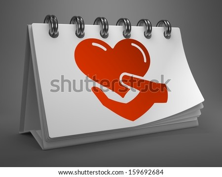 White Desktop Calendar with Red Icon of Heart in the Hand on Gray Background. Charity Concept. - stock photo