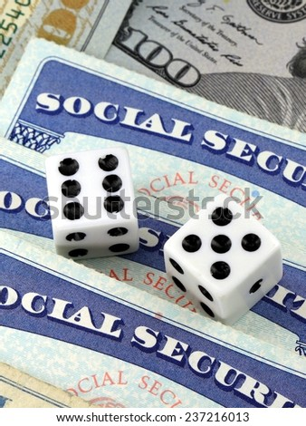 White Dice Laying on Social Security Card - Gambling on benefits and retirement income