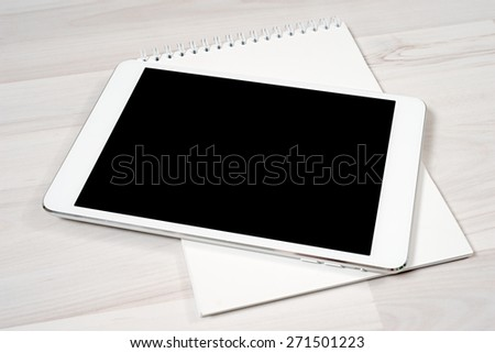 White digital tablet on wooden table