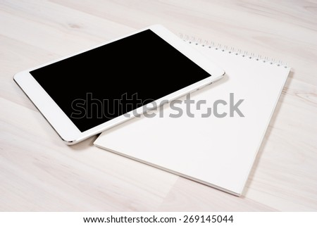 White digital tablet with pen and notebook on the table - stock photo