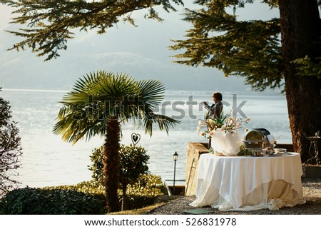 White dinner table stands under the green tree at the sea coast