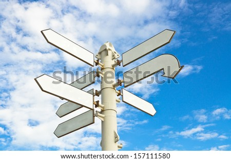 White direction notice under blue sky - stock photo