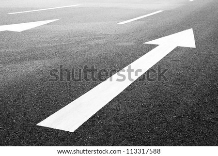 white directional arrow on blacktop