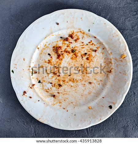 White dirty plate after spaghetti pasta with meat and tomato sauce. Red sauce spots on dish area. Stone background - stock photo