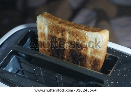 White dirty toaster and burned toast (selective focus, dark tone) - stock photo