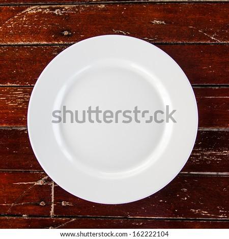 white dish on grunge dark brown wood table - stock photo