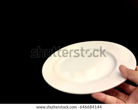 White dish on hand and the Black background.