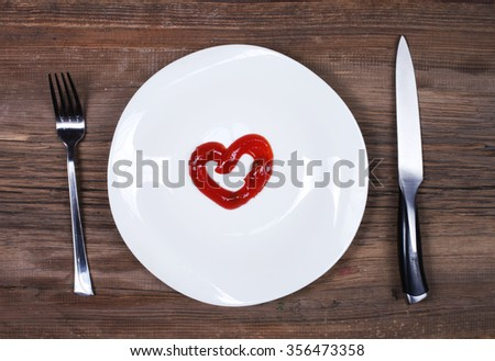 White dish with ketchup shaped as heart, knife and fork