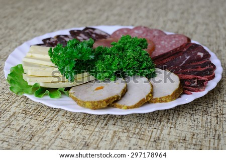 White dish with meat and salami appetizer. Decomposition evenly coats. Plate stands on a table covered with a tablecloth. - stock photo