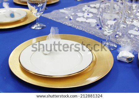 White dishes on blue tablecloth - stock photo