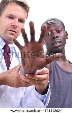 White doctor examines tendons of extended hand and wrist of young athletic black patient on white background - stock photo