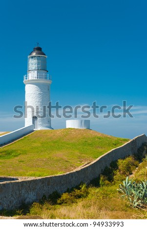 White Dongju Lighthouse stands atop a rolling hill enclosed by a brick wall on Juguang Island on a clear sunny, blue sky day on Matsu Islands in Taiwan. Vertical copy space