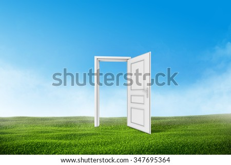 White door on a green grass field with blue sky background. - stock photo