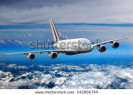 White double decker passenger plane in the blue sky. Aircraft flies high over the clouds and snow-covered mountain landscape. Airplane front view.