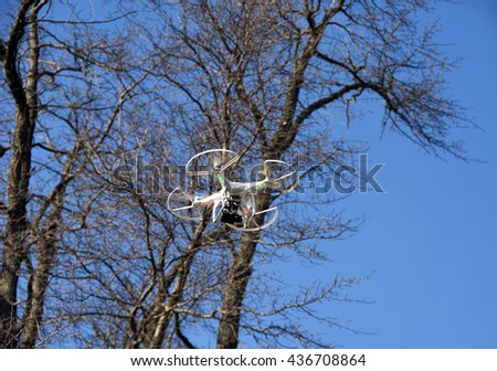 white drone with camera in spring time trees with bright blue sky background - stock photo