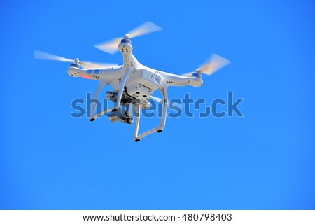 white drone with video camera in bright blue sky