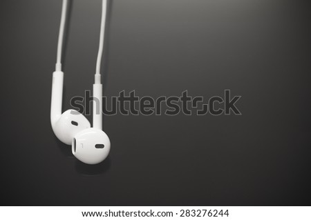 White earbuds on black screen background - stock photo