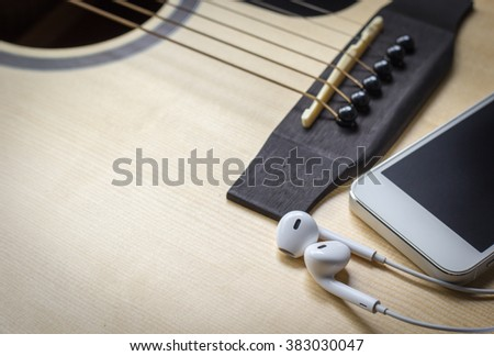white earphone and smart phone on the guitar