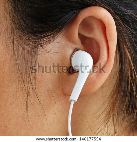 White Earphone in a Girl's Ear - stock photo