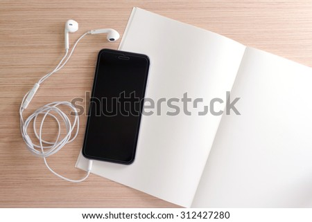 white earphone, smartphone, paper, book, note on wooden background with copy space - vintage effect style picture - stock photo