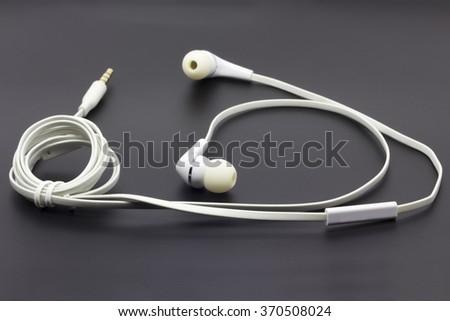 White earphones on the black isolated background - stock photo