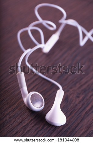 White earphones over a dark wooden background - stock photo