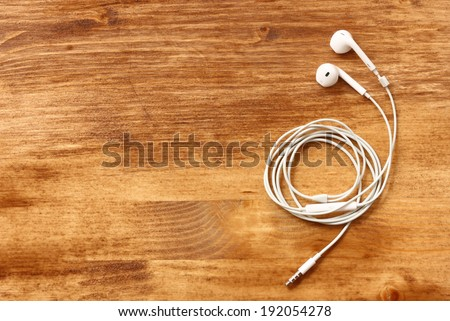 white earphones over wooden board - stock photo