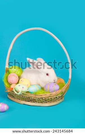 white Easter bunny with basket and colored eggs - stock photo