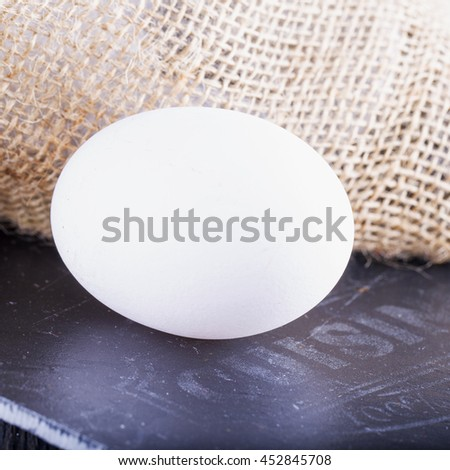 White egg over black stone chopping board, square image - stock photo