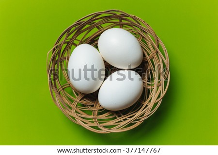 White eggs in a basket isolated on a green background in center. Design, visual art, minimalism