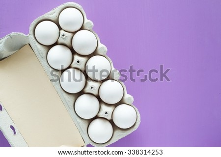 White eggs in a cardboard over purple painted wooden background, top view