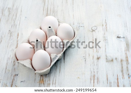 White eggs on a wooden background - stock photo