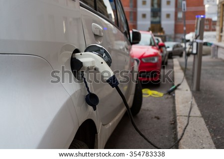 White electric car charging in the streets of Oslo, Norway - stock photo