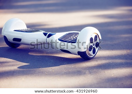 White Electric mini hover board scooter on asphalt road. Eco city transportation on battery power, produce no air pollution to atmosphere - stock photo