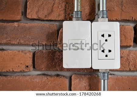 White electric socket on red brick wall. - stock photo