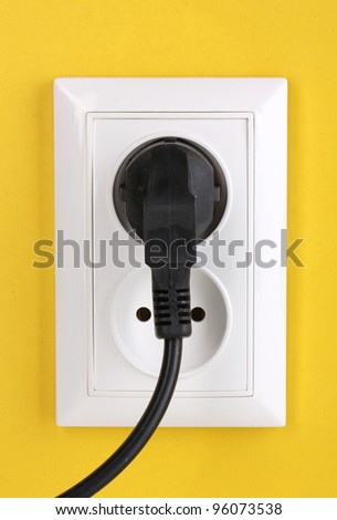 White electric socket with plug on the wall