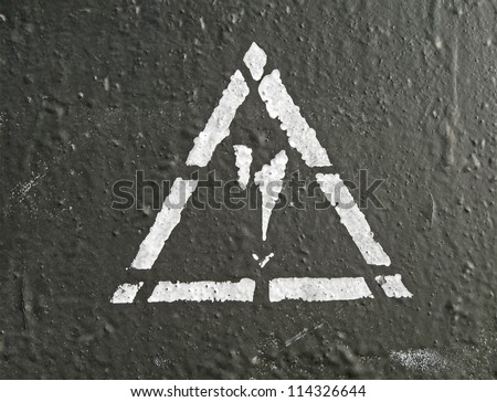 white electricity danger sign on black painted wall, power details - stock photo