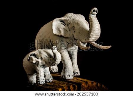 White elephant mother and baby wooden elephant on black background - stock photo