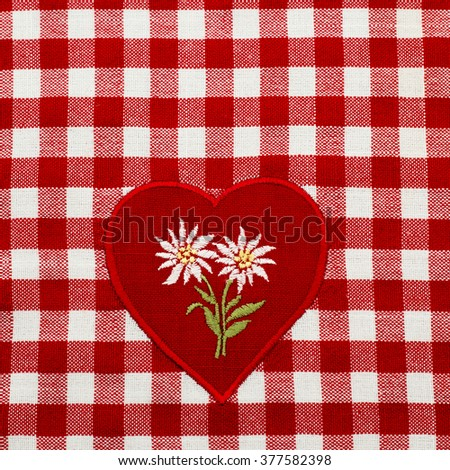 White embroidered Edelweiss flower on heart appliques on the checkered red white tablecloth - stock photo