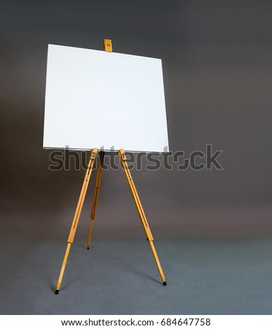 White empty artistic canvas on an easel for drawing images by an artist on a gray background in the studio. Background