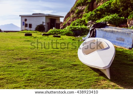 White empty boat rowing on the green grass near the mountain on a background the boathouse. - stock photo