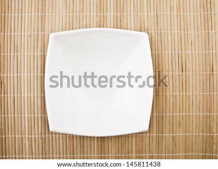 white empty bowl on a bamboo table top Copy space for inscription - stock photo