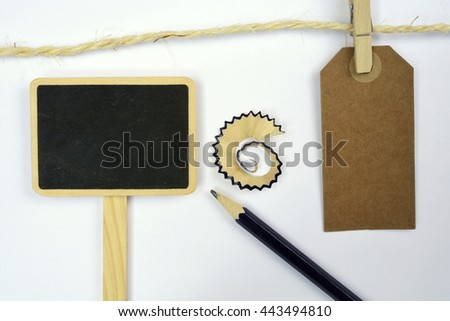 White empty copy space background with black wooden pencil with sawdust of a sharpener and tag - stock photo