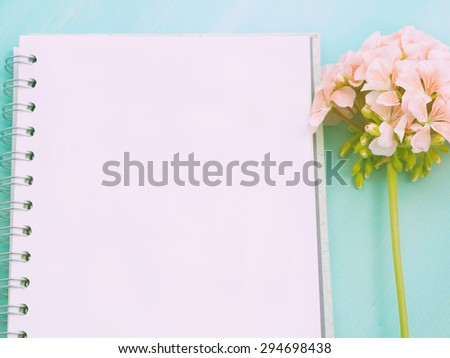 White empty page of an open notebook with a geranium flower put on green pastel wooden table